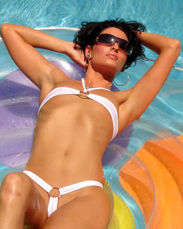 brune prend le bain de soleil en mini bikini blanc