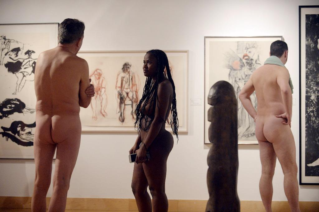 femme noire nue et deux hommes nus regardent l'expo nu