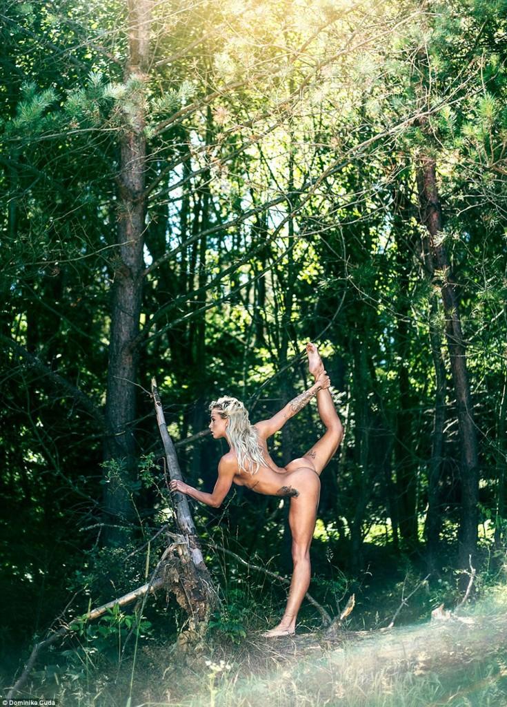 une blonde sportive tatouée pose nue dans la forêt
